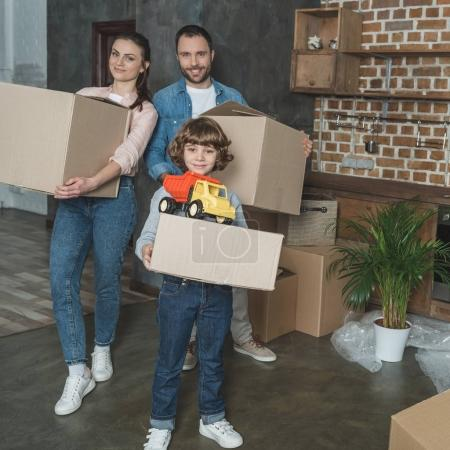 Photo for Full length view of happy family with boxes and toy smiling at camera while relocating - Royalty Free Image