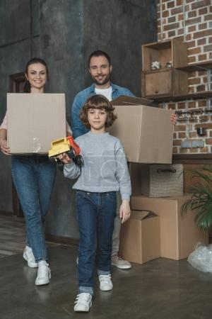 happy family with boxes and toy smiling at camera while moving home