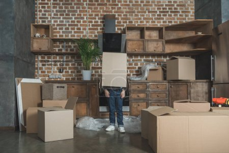 Photo for Little boy standing with cardboard box on head while moving home - Royalty Free Image