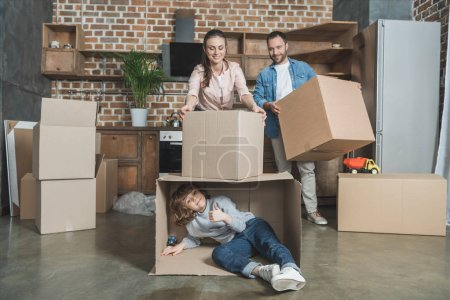 Photo for Happy family packing boxes while moving home - Royalty Free Image