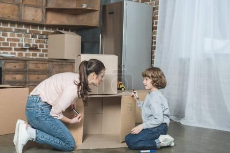 Photo for Side view of mother and son drawing on cardboard box in new apartment - Royalty Free Image