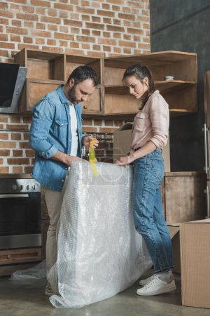 young couple packing picture while relocating