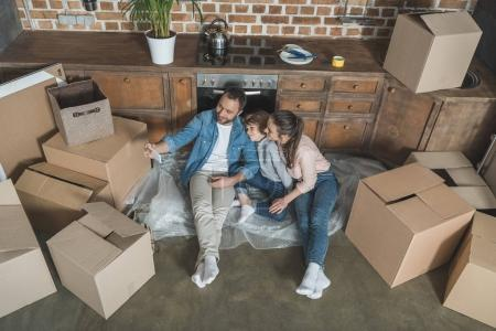 high angle view of happy family taking selfie with smartphone while moving home