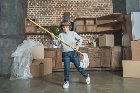 cute happy little boy playing with mop in new apartment