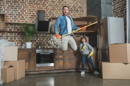 happy father and little son having fun together in new apartment