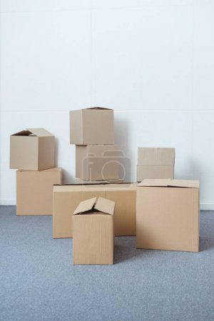 Photo for Stacked cardboard boxes in empty room during relocation - Royalty Free Image