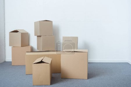 stacks of cardboard boxes in empty room during relocation