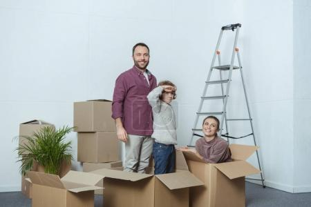 Photo for Happy family with one child having fun with cardboard boxes during relocation - Royalty Free Image
