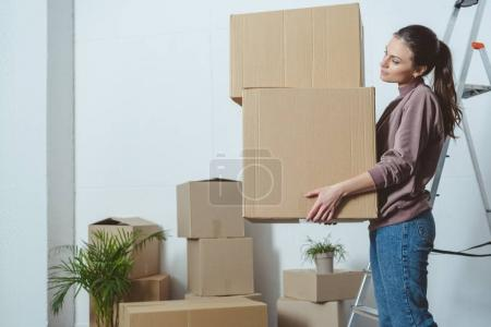 side view of young woman holding stack of boxes while moving home