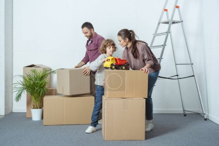 Photo for Family with one kid packing cardboard boxes while moving home - Royalty Free Image