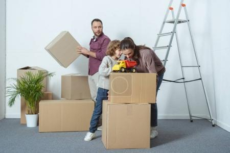 Photo for Family with one child packing cardboard boxes while moving home - Royalty Free Image