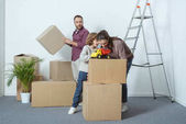 family with one child packing cardboard boxes while moving home