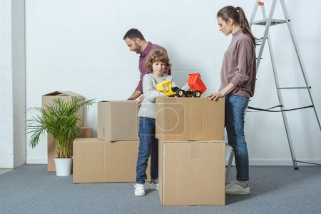 Photo for Happy family with one child packing cardboard boxes during relocation - Royalty Free Image