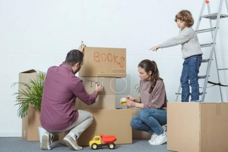 parents packing boxes and son pointing with finger during relocation
