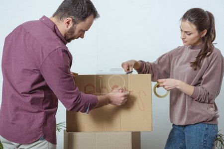 Photo for Young couple packing boxes while moving in new house - Royalty Free Image