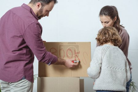 family with one kid singing cardboard box while moving in new home