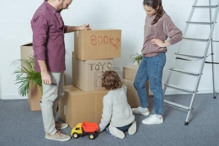 cropped shot of happy family with one child signing boxes while moving in new home