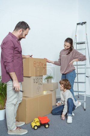 Photo for Happy family packing boxes while moving in new home - Royalty Free Image