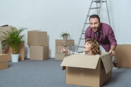 father and son in cardboard box having fun together while relocating