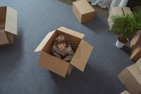 high angle view of little boy sitting in box and looking at camera during relocation