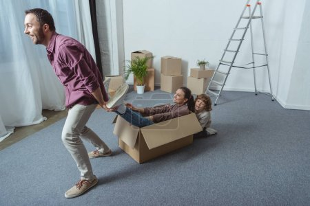 happy father and son having fun with mother sitting in cardboard box