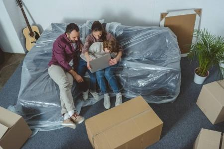 Photo for High angle view of family with one child using laptop while moving in new home - Royalty Free Image