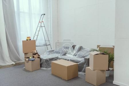 Photo for Stacked cardboard boxes, ladder and toys in empty room during relocation - Royalty Free Image