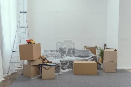 Photo for Cardboard boxes, ladder and toys in empty room during relocation - Royalty Free Image