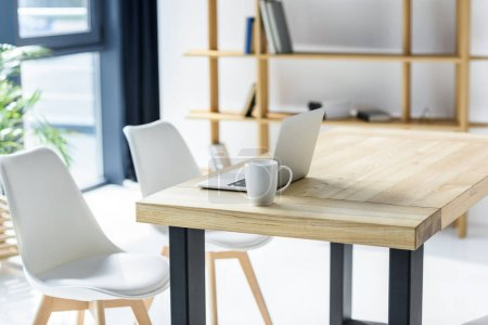 Photo for Laptop and coffe cup on table in modern office - Royalty Free Image