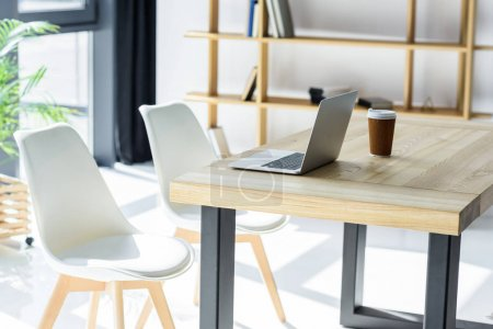Photo pour Ordinateur portable et tasse de café sur la table dans le bureau moderne - image libre de droit