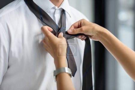 Woman helps man to tie a knot on tie
