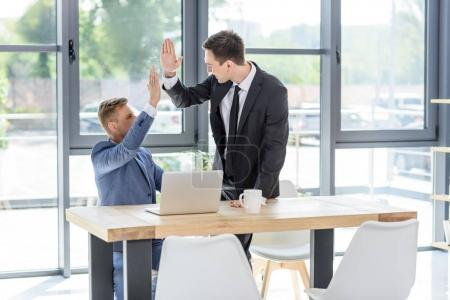 Successful businessmen giving high five by laptop in modern office