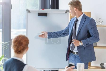 Young businessman presenting his idea by flip chart to colleagues in modern office