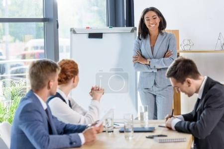 Photo for Young businesswoman presenting her idea to colleagues in modern office - Royalty Free Image