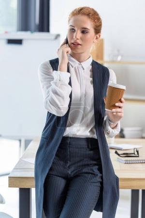 Photo pour Femme avec une tasse de café dans les pourparlers de mains sur smartphone au bureau - image libre de droit