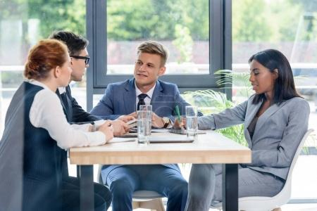 Behind the glass view of executives discussing project in modern office