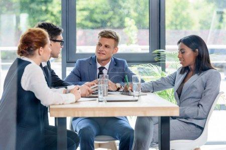 Derrière la vue en verre des cadres discutant du projet dans le bureau moderne