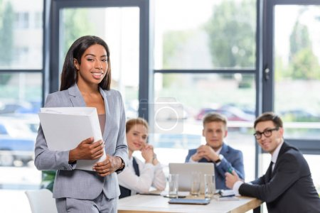 Confident businesswoman with folder in hands in front of his colleagues in modern office