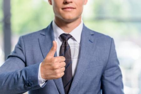 Young businessman showing thumb up gesture