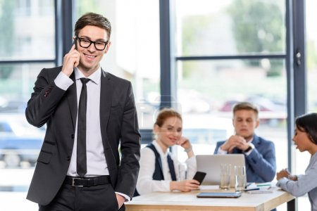 Smiling businessman talking on smartphone in front of his colleagues in modern office