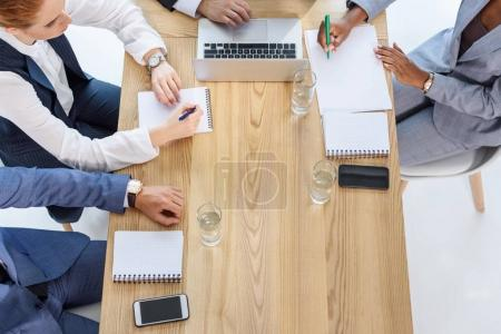Business team writing in notepads during meeting in office