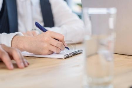 Man writing in notepad during meeting in office