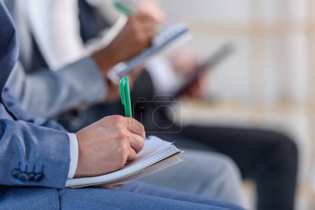 People with notepads listening to presentation in modern office