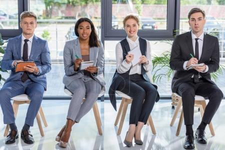 Businessmen and businesswomen with notepads listening to presentation in modern office