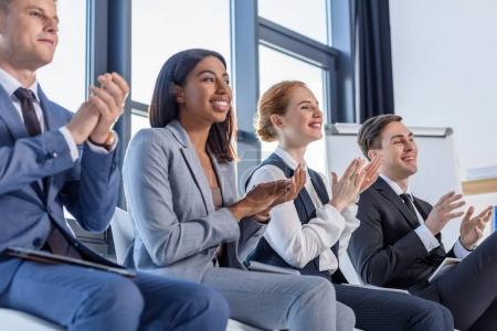 Young colleagues applauding to presentation in modern office