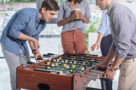 Young businessmen playing table football in modern office