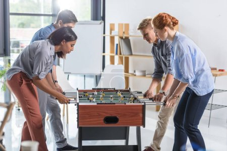 Colleagues playing table football in modern office