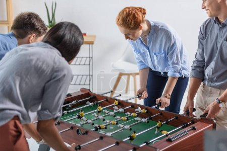 Young team playing table football in modern office
