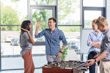 Business people playing table football during break in modern office