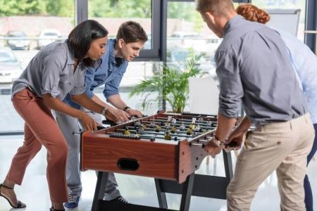Young people playing table football in modern office